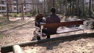 Kuvassa isä istuu puiston penkillä ja nukuttaa lasta vaunuissa.