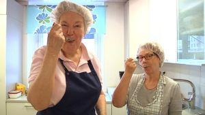 Kaksi naista maistavat lusikalla ruokaa.