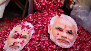Hindunationalistisen BJP-puolueen Narendra Modia esittäviä naamareita ruusupedillä.