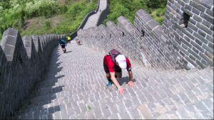 Kilpailija kiipeää muuria eteenpäin.