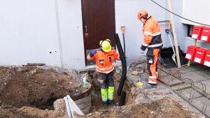 Työmiehiä taloyhtiön pihalla kuopassa.