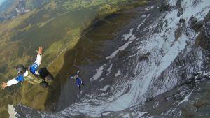 Base-hyppääjät ilmalennossa kallioseinämän kohdalla.