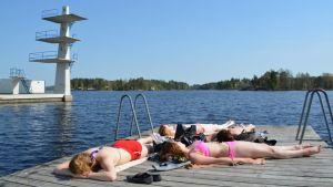 Nuoria naisia ottamassa aurinkoa uimarannan laiturilla.