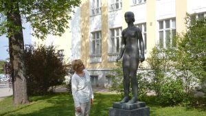 Hämeenlinnan taidemuseon amanuenssi Päivi Viherluoto ja Victor Janssonin patsas Nuoruus (1931) Hämeenlinnassa