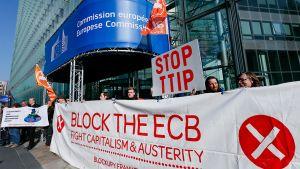 Kansalaisjärjestöt osoittavat mieltään EU:n ja Yhdysvaltain välistä vapaakauppasopimusta vastaan EU-komission edustalla sopimusneuvottelujen aikana.