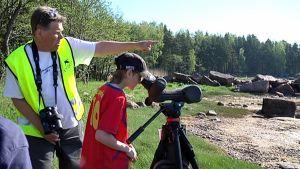 Koulupoika katselee kaukoputkella muuttavia lintuja.