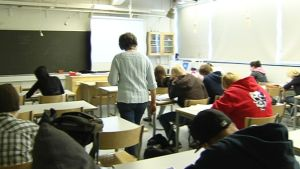 Opettaja kävelee luokassa.
