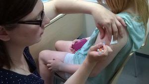 Terveydenhoitaja laittaa tytölle rokotteen käsivarteen