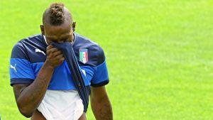 Italian Mario Balotelli pyyhkii kasvojaan paidallaan.