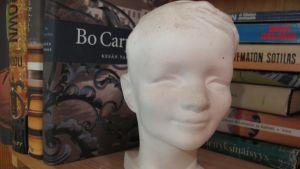Hymypoika-patsas kirjahyllyssä