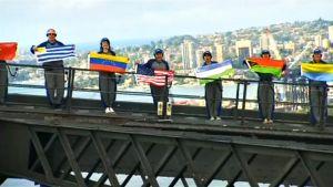 Ihmisiä sillalla maiden lippuja käsissä.