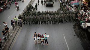 Neljä ihmistä osoittaa mieltään sotilaiden edessä Bangkokissa.