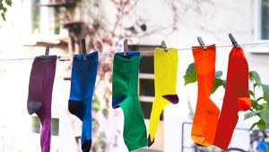 Kuvassa erivärisiä sukkia pyykkinarulla.