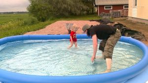 Isä ja tytär kahlaavat uima-altaassa