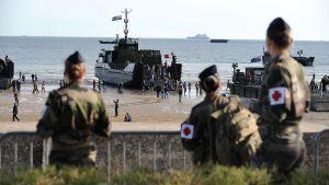 Ihmisiä Arromanchesin rannalla katsomassa Britannialaisten joukkojen kalustoa.