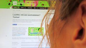 Nainen koneen äärellä, netissä auki Ylen suosittu suomalaisuustesti.