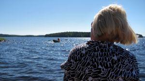 Nainen (selin) istuu järven rannalla, katselee järvellä olevaa soutuvenettä.