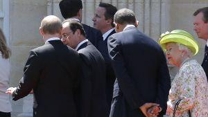 Ranskan Normandian maihinnousun 70-vuotismuistojuhlien tauolla Venäjän presidentti Vladimir Putin keskustelee Ranskan presidentti Hollanden kanssa. Heidän takanaan rupattelevat Yhdysvaltain presidentti Barack Obama ja Englannin kuningatar Elisabet II. Englannin pääministeri David Cameron näkyy taustalla.