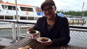 Pitopalveluyrittäjä ja gastronomian sekatyömies Santeri Vuosara laivan kannella ruoka-annosten kanssa.