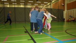 Lapset pelaavat liikuntasalissa.