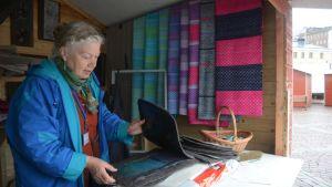 Sotkamolainen Leila Viitala järjestelee käsitöitään myyntikojussaan.