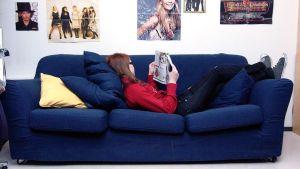 Nuori nainen lukee lehteä sohvalla.