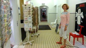 Nainen seisoo käytävällä, missä myyntitelineissä postikortteja.