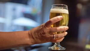 A glas of beer in a women's hand.