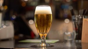 Beer in a stemmed glass on a bar.