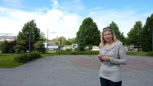 Nainen seisoo puistossa. Taustalla puita ja autoja.