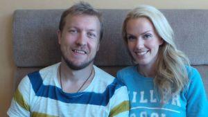 Niklas ja Piritta Hagman istuvat sohvalla ja hymyilevät.