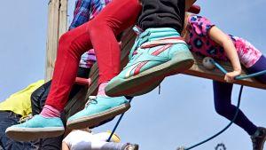 Lasten jalkoja kiipeilytelineellä.