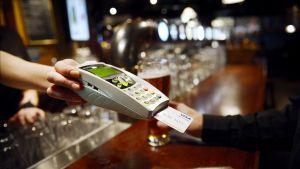 Mies maksaa luottokortilla ravintolassa.