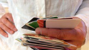 Etukortteja ja muita lompakosta löytyneitä kortteja kädessä.