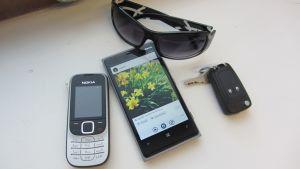 vanha puhelin, älypuhelin, aurinkolasit ja auton avaimet