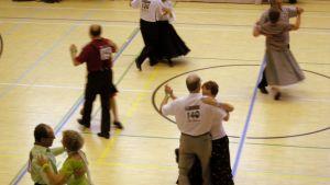 Tanssipareja tanssikisoissa liikuntasalissa