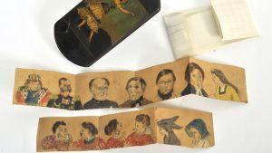 Gallen-Kallelan esineistöä, kirjelappu, piirrettyjä ihmisiä sekä puukotelo