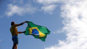 Mies heiluttaa Brasilian lippua.