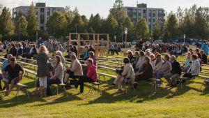 Ihmisiä istumassa penkkiriveillä nurmikentällä.