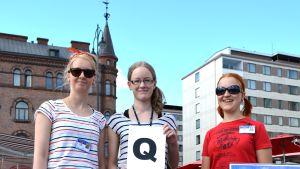 Kolme nuorta naista ja q-kirjainkyltti torilla