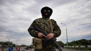 Venäläismielinen taistelija vartioi tarkastuspisteellä lähellä Donetskia sunnuntaina.