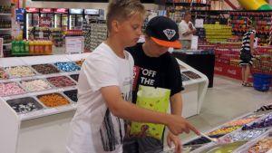 Kaksi poikaa valitsemassa irtokarkkeja.