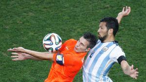 Hollannin Robin van Persie ottaa pallon haltuun. Argentiinan  Ezequiel Garay varjostaa.