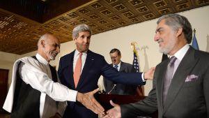 Afganistanin presidenttiehdokkaat Ashraf Ghani (vas.), Abdullah Abdullah (oik.), sekä Yhdysvaltain ulkoministeri John Kerry (kesk.) kättelevät vaalitulosten uudestaan laskentaa koskevassa tiedoitustilaisuudessa Kabulissa 12. heinäkuuta 2014.