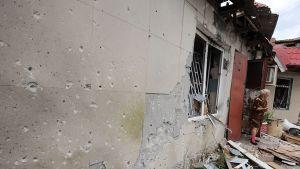 Nainen katsoi pommitusten tuhoja talonsa edessä Maryinkan kylässä, Donetskin lähellä lauantaina.