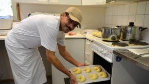 Ali Abdelbakylaittaa pullia uuniin kahvila Kuhveikon keittiössä.