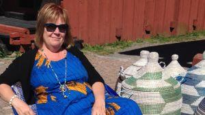 Suomentaja Jaana Kapari-Jatta istuu afrikkalaistuolissa vierellään kannellisia koreja Senegalista