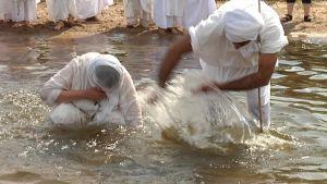 Miestä kastetaan vedessä