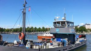 Harmaa parikymmenmetrinen saaristotankkeri on kiinnittyneenä Liuskaluodon laituriin. Musta letku johtaa aluksesta maihin.