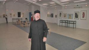 Äitinsä Ina Collianderin teoksia esittelee Valamon luostarin näyttelysalissa rovasti Sergius Colliander.